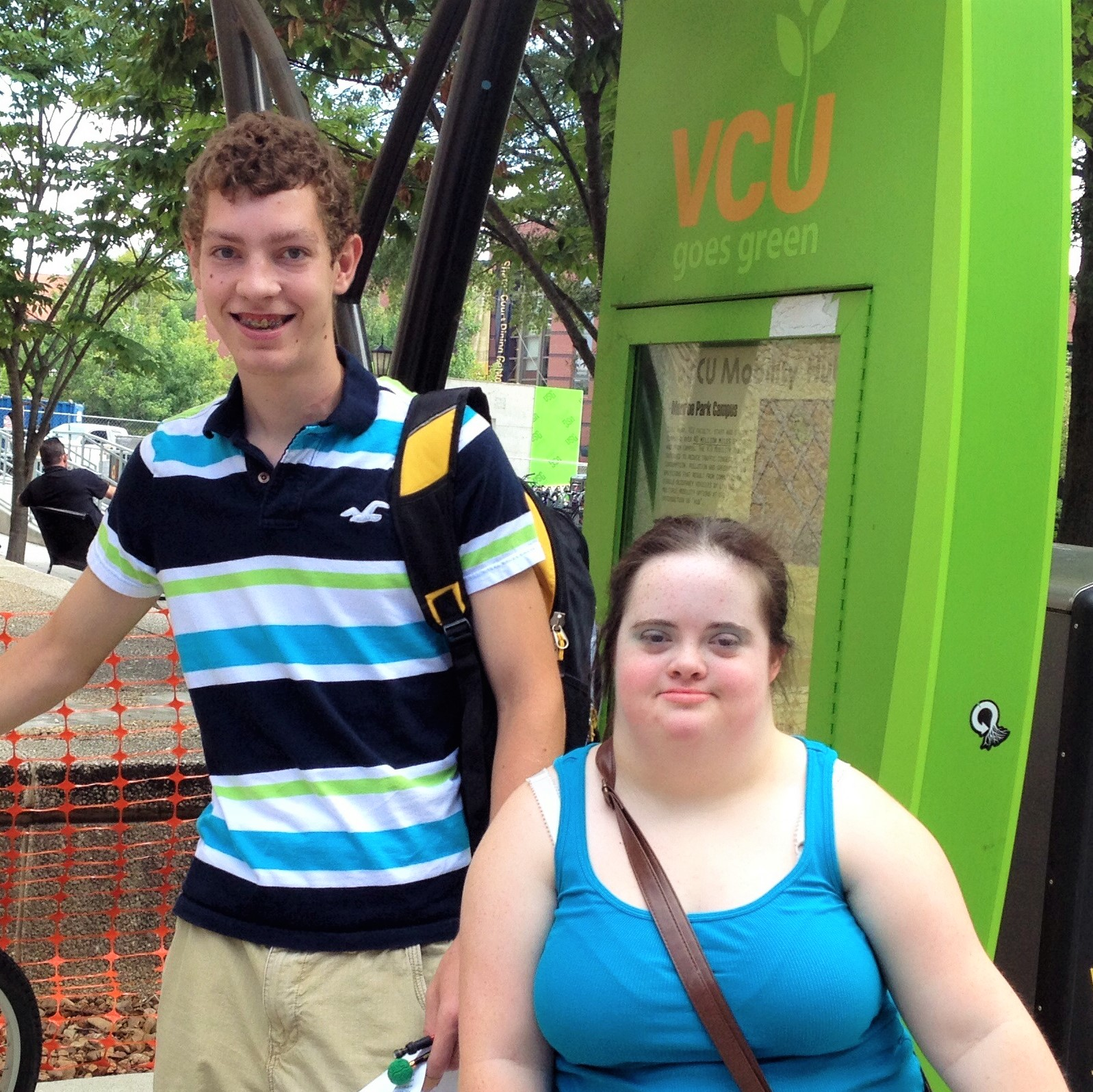 Grace and Bryan standing in front of a VCU 'Go Green' stop'